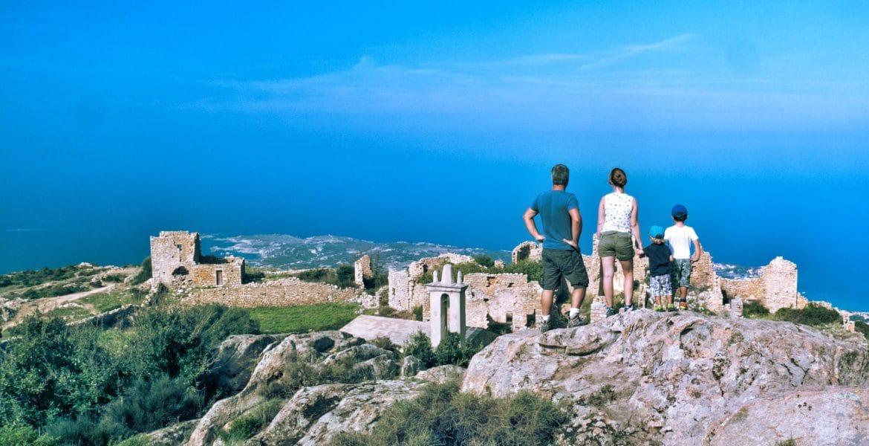famille de dos devant le village en ruine d'Occi et la mer