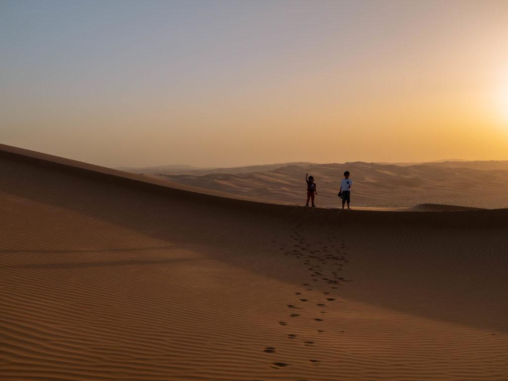 2 enfants sur la crète de la dune devant le coucher de soleil